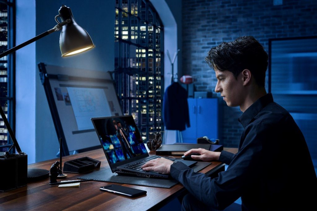 A person sitting at a desk using a computer  Description automatically generated with medium confidence